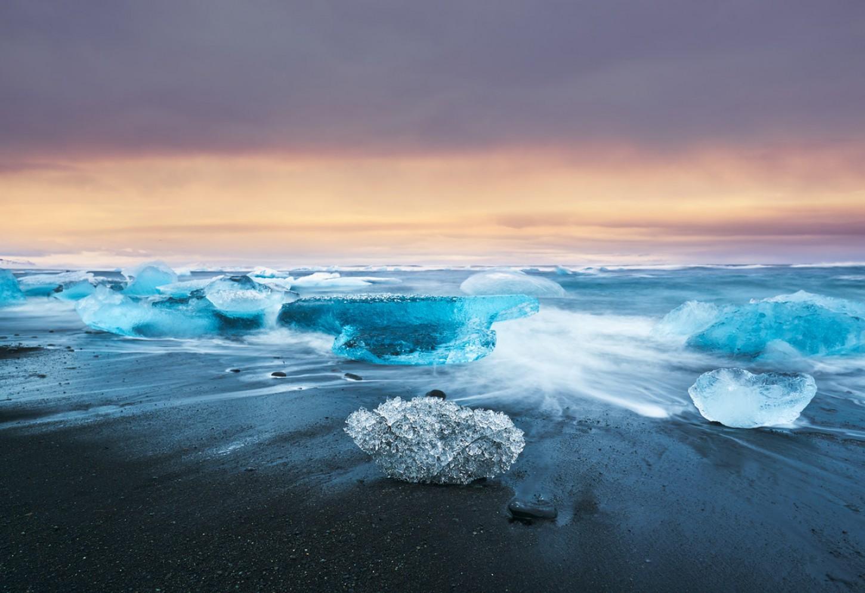 Diamanten ijsschotsen op een pikzwart strand Kriski